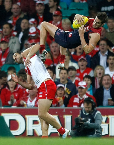 Jeremy Howe of Melbourne flies high over Heath Grundy (photo: Triple M)