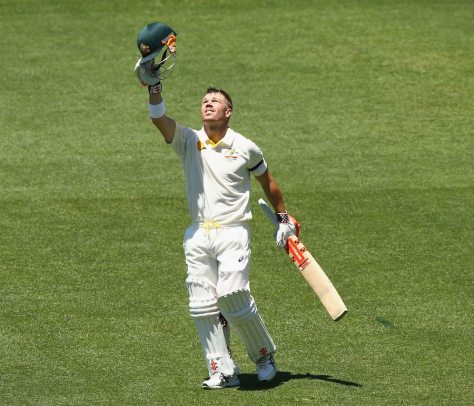 David Warner holds his helmet high dedicated to Phil Hughes as he celebrates a century (photo: Getty Images)